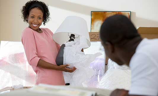 smiling couple unpacking lamp