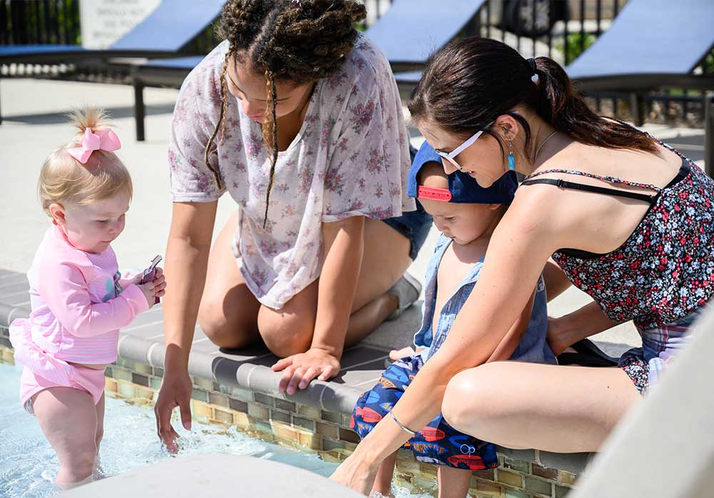 women with kids playing in pool