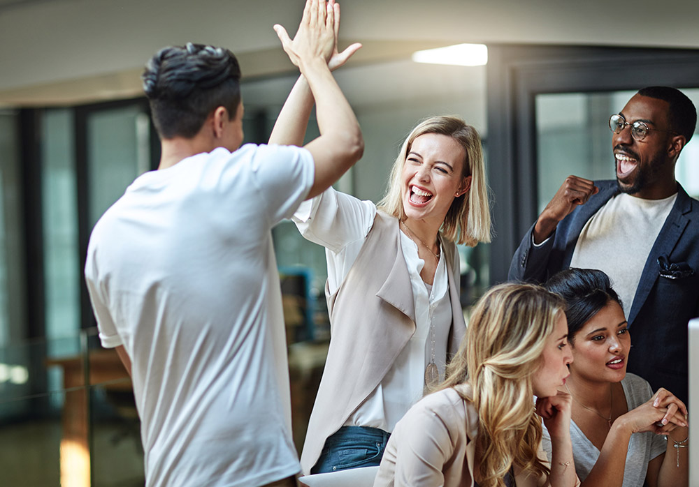 Coworkers High Fiving at their workplace in Rochester, MN