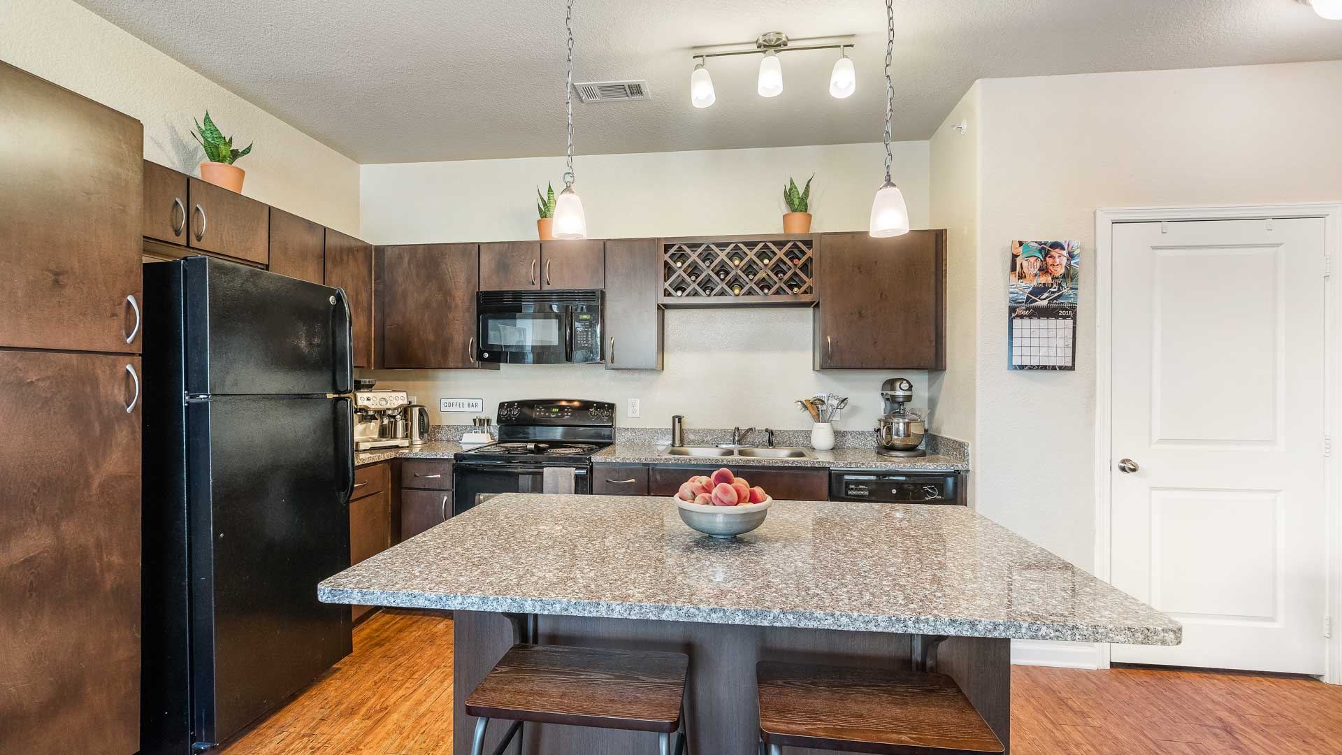 Kitchen with Island Counter and black appliances in San Antonio at Springs at Alamo Ranch