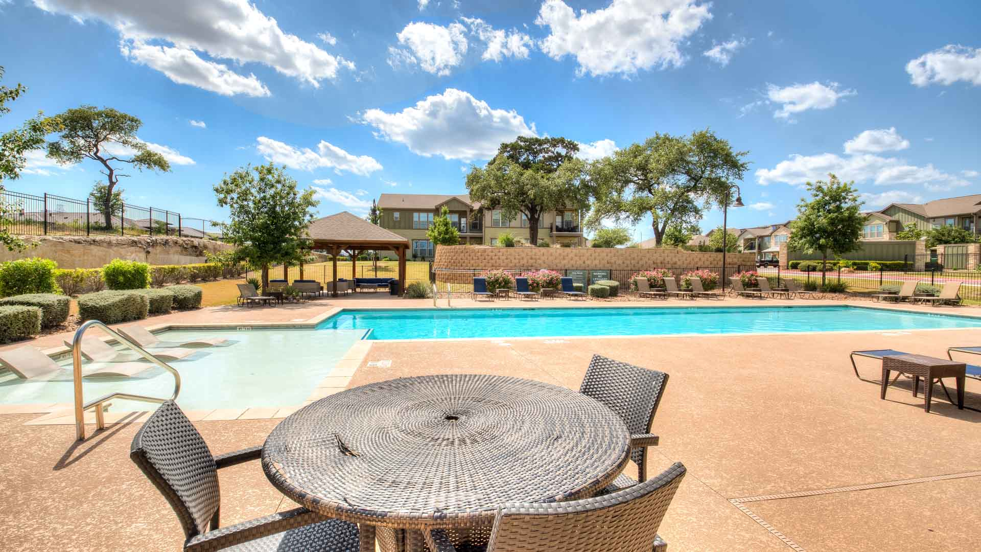 Tables near the pool in San Antonio at Springs at Alamo Ranch