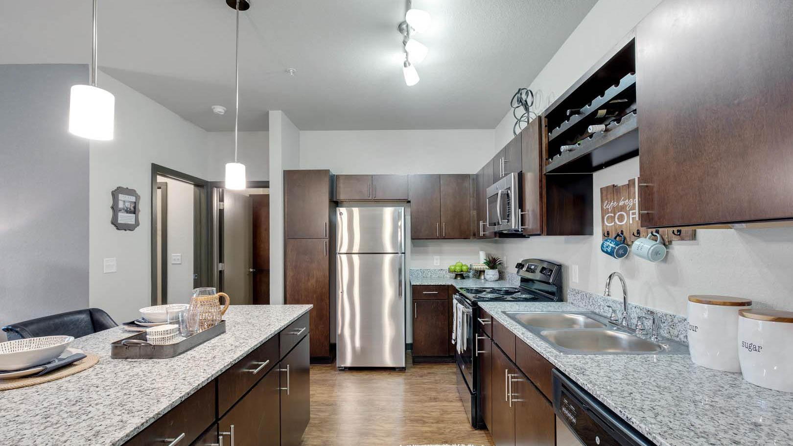 Kitchen with wood cabinents and stainless steel fridge at Springs at Round Rock in Austin Texas