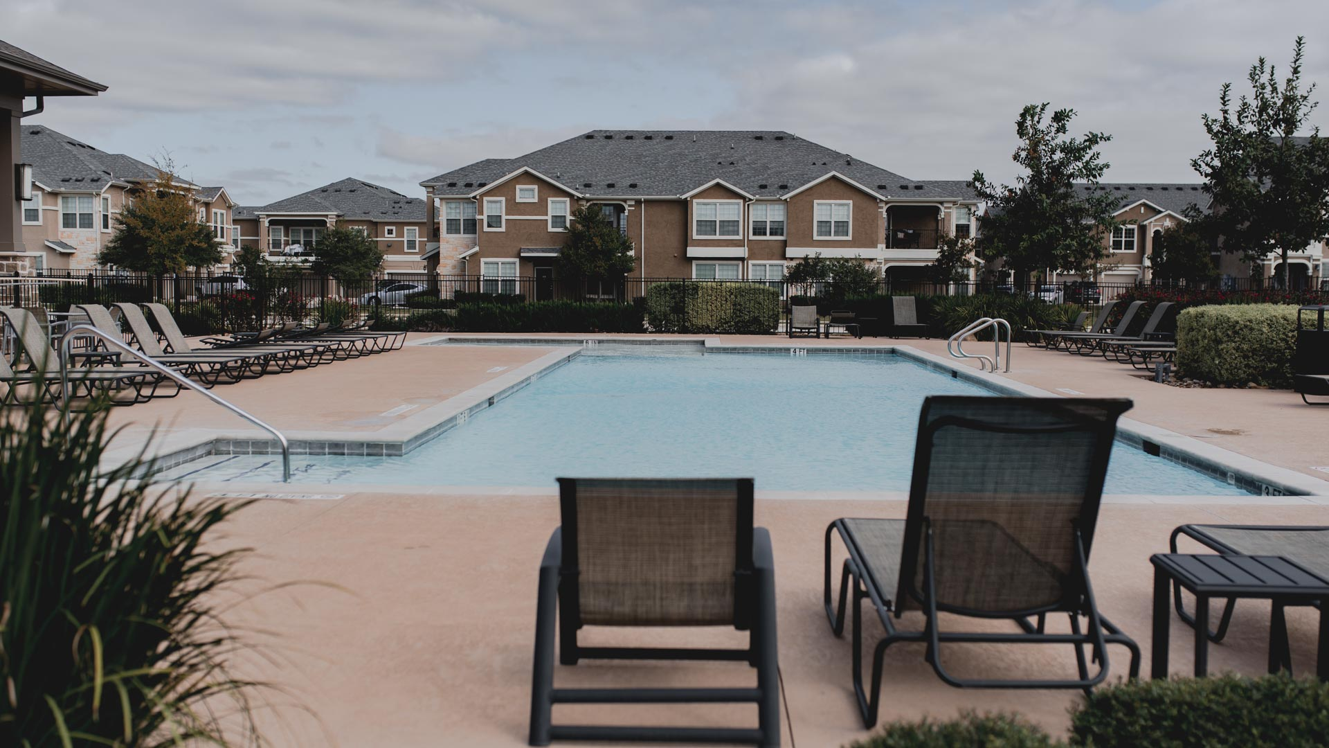 Pool with lounge chairs at Springs at Creekside in New Braunfels, TX