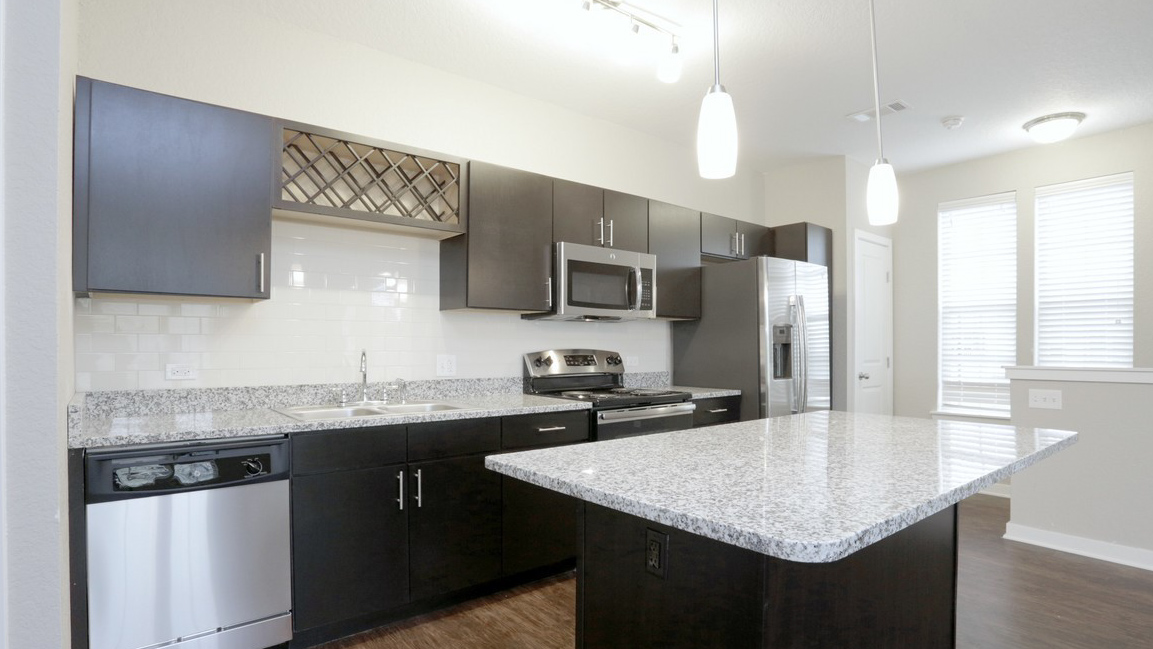 Open Concept Kitchen with granite and stainless steel in Romeoville, IL at Springs at Weber Road-41